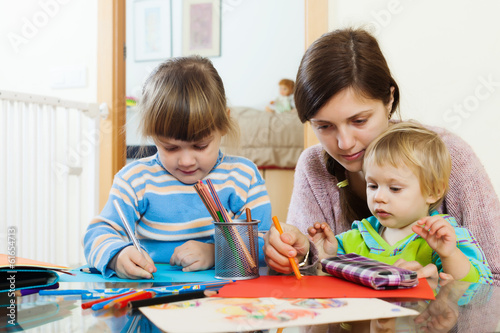 serious mother and children sketching with pencils