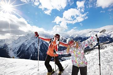 Happy woman and girl on mountains ski resort