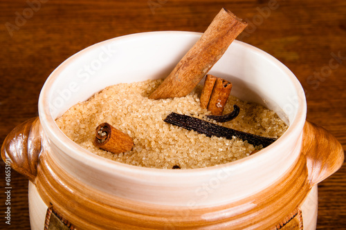 Brown sugar and spices on dark wooden background