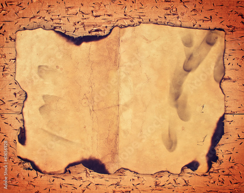 Burnt old paper on wooden grungy background