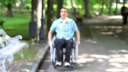 Young man in wheelchair alone in the city park