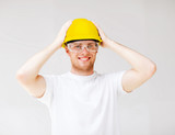male builder in safety glasses and yellow helmet