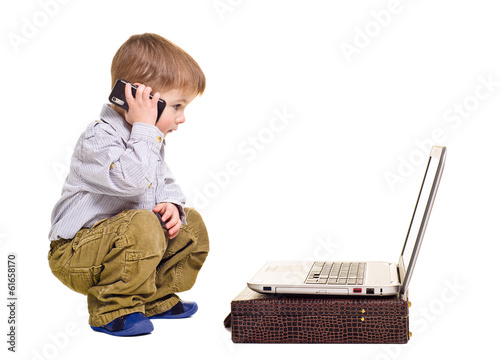Attractive boy speaks on the phone looking at laptop
