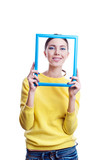 Young beautiful woman holding light blue frame