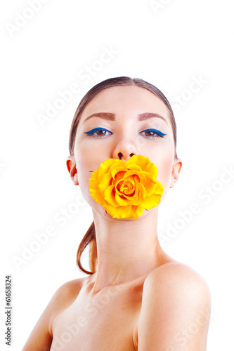 Beautiful woman with yellow rose flower in her mouth