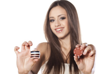smiling girl holding a gambling chips in her hands