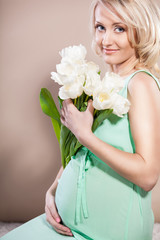 Pregnant woman holding in hands bouquet of flowers