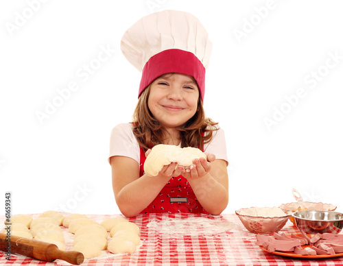 happy little girl cook with dough