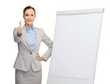 smiling businesswoman standing next to flip board