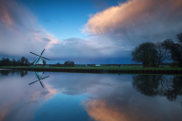 Dutch windmill at stormy sunset