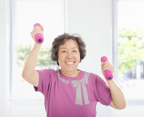 happy senior woman working out with dumbbells at home