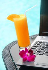 Black laptop and orange juice poolside