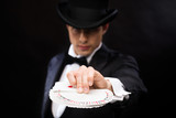 magician in hat showing trick with playing cards