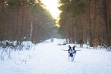 French bulldog in winter jacket on the walk in forest