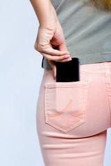 Black smartphone in back pocket of girl's jeans