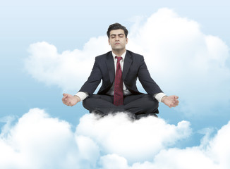 Business man meditates on clouds
