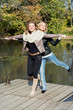 Two attractive women posing by the pond in the autumn park