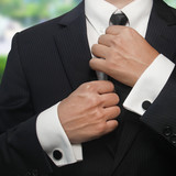 a man in a black suit straightens his tie