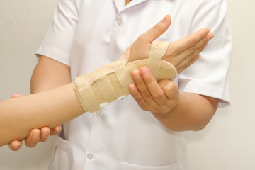 doctor putting wrist  brace on the patient's arm