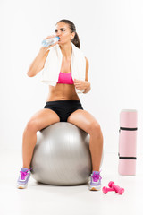 Fitness woman sitting to pilates ball and drinking water.