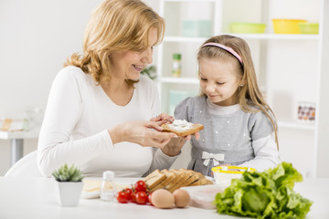 Cute little girl with Grandmother making a Sandwich.