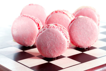 Pink French macarons on a chessboard