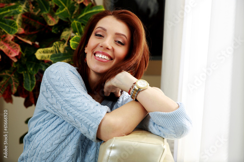 Happy woman leaning on the sofa at home