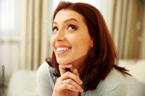Smiling woman looking up at home