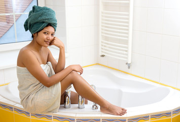 Young woman sitting on the bathtub