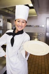 Smiling female cook holding an empty plate in kitchen