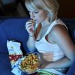 Twen vor Fernseher isst Fast Food