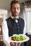 Waiter showing bowl of salad to camera