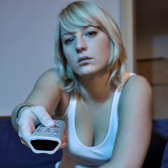 Frau mit Fernbedienung vor TV Gerät