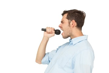 Side view of a young man singing into microphone