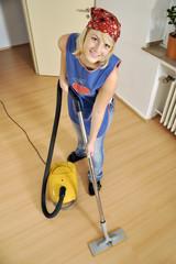 Putzfrau mit Staubsauger bei Hausarbeit