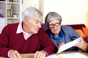 Senior couple reading bills at home
