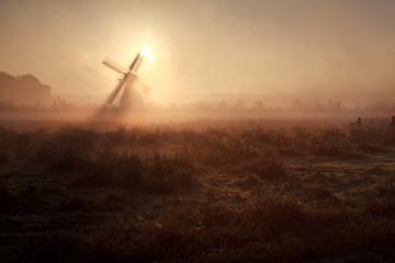 sunshine behind windmill in misty morning