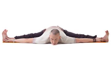 Yogi posing on split, isolated over white backdrop