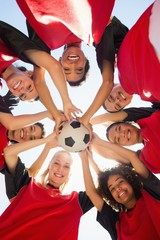 Soccer team with ball forming huddle against sky
