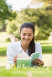 Smiling woman reading a book in park