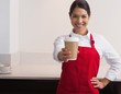 Pretty young barista offering cup of coffee to go smiling at