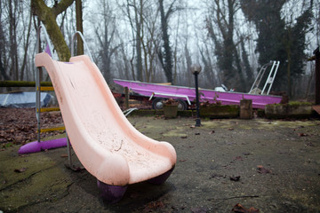 Abandoned playground in a misty wood