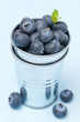 Fresh blueberries in a metal bucket on a blue background
