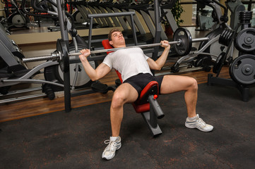 Young man doing Barbell Incline Bench Press workout in gym