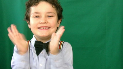 Boy clapping in front of a green screen