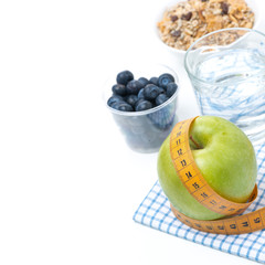 healthy food concept - apple, blueberry, water and muesli