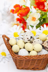 wicker basket with easter eggs and flowers