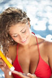 Sunscreen beach woman in bikini applying sun block solar cream f