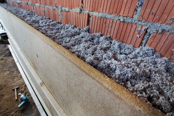dry cellulose fiber blown-in in front of a brick masonry