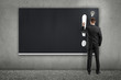 man drawing exclamation mark on blackboard